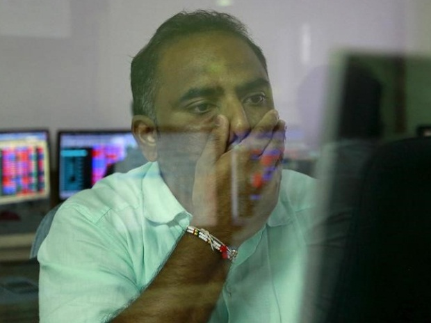 A broker reacts while trading at his computer ...