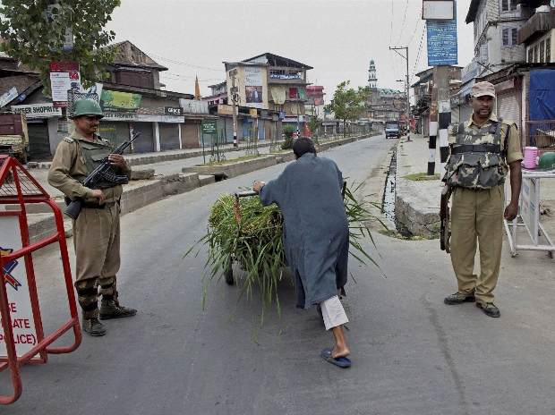 A labourer pulls a handcart while Security jawans guard the streets during curfew and strike in Srinagar
