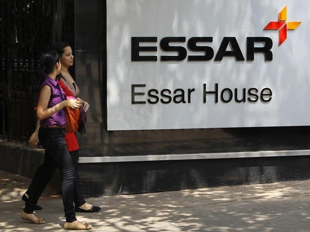 Employees walk past an Essar Group logo outside their headquarters in Mumbai