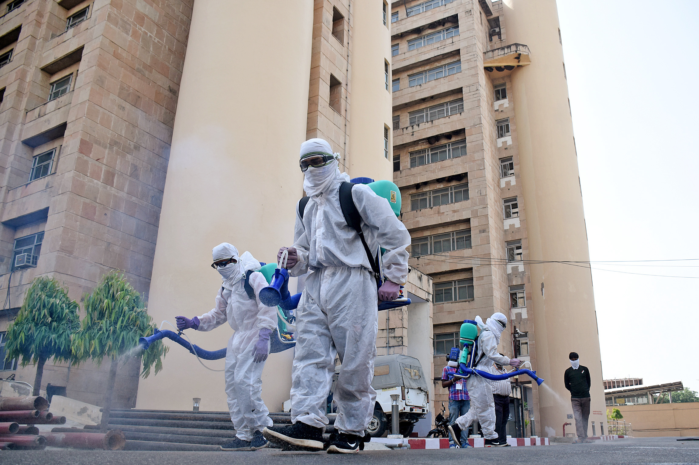 Municipal workers spray disinfectant at Bapu Bhavan Secretariat building as government-imposed nationwide lockdown to take preventive measures against the spread of the Coronavirus, in Lucknow on Sunday.
