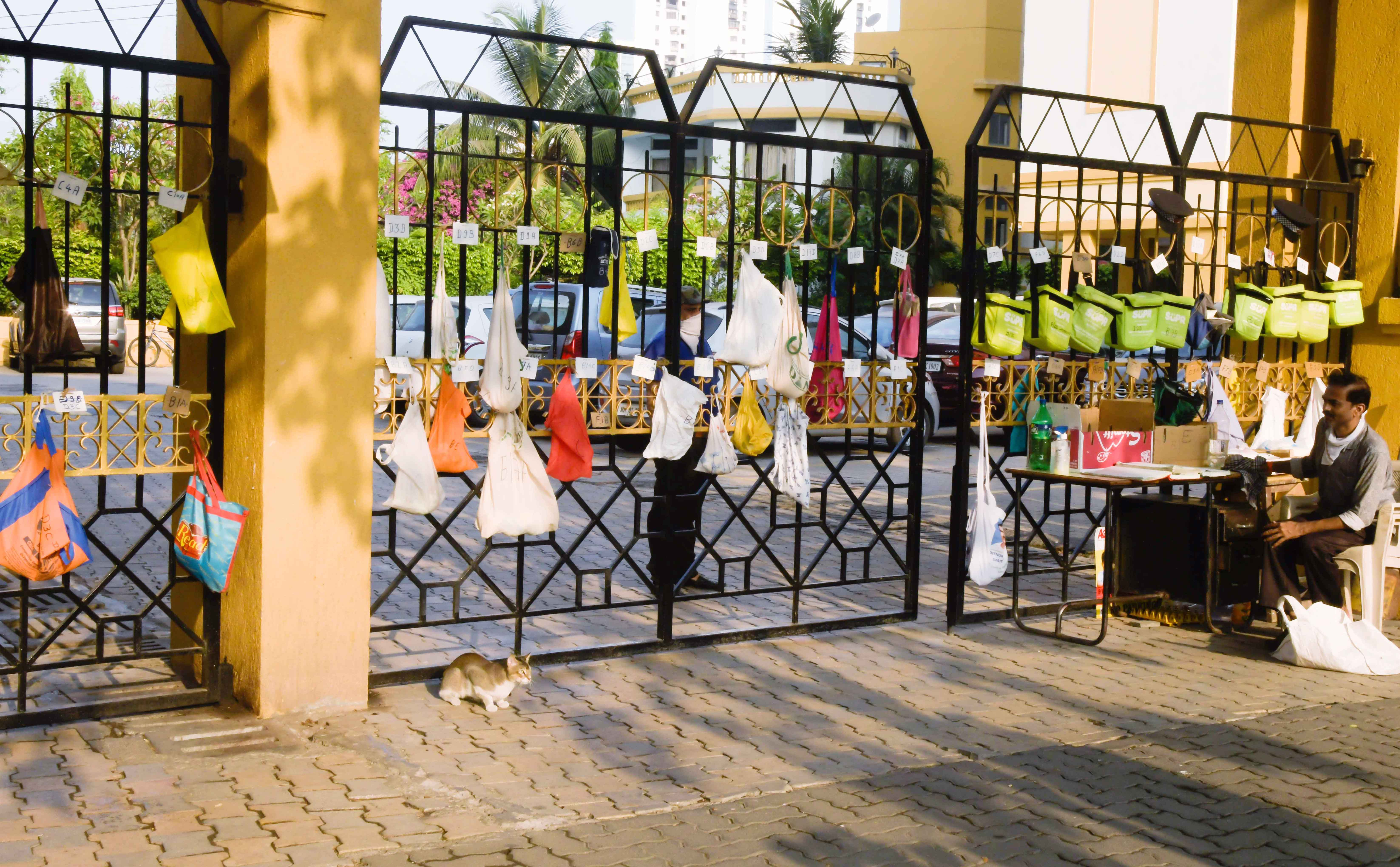 Bags for the milkman to drop in milk pouches hang on the gate of a residential complex during a nationwide lockdown to control the spread of the coronavirus, in Mumbai on Sunday.